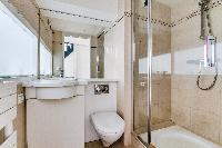 pale-painted bathroom with shower, toilet, and sink in a studio apartment in Paris