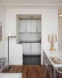 a dining area with a white table and clear dining chairs for 4, and well-equipped kitchen in a 1-bed