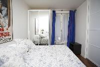 cozy bedroom with a queen-size bed, a bedside table, a cabinet, and a television in a 1-bedroom Pari