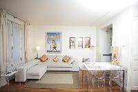 cozy living area with an L-shaped couch that doubles as a sofa bed, and a dining area in a 1-bedroom