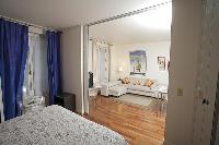 cozy living area with an L-shaped couch and bedroom in a 1-bedroom Paris luxury apartment