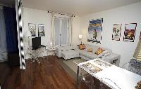 cozy living area with an L-shaped couch and a dining area in a 1-bedroom Paris luxury apartment
