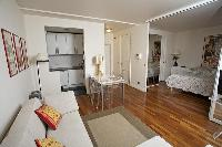 cozy living area, dining area, bedroom, and kitchen in a 1-bedroom Paris luxury apartment