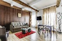spacious and bright living area with a sofa, armchairs, and a television in a 2-bedroom Paris luxury