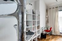 unique and modern spiral staircase, shelves, and study desk and chair in a 1-bedroom loft Paris luxu