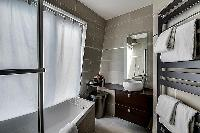 contemporary bathroom with toilet, sink, towel rack, and a bathtub with a detachable shower head in