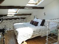 sleeping area with a queen-size bed, two bedside tables, a fan, and a skylight in a Paris luxury apa