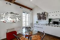 three-seater dining set and a sofa in a 1-bedroom loft Paris luxury apartment