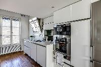 well-equipped white kitchen in a 1-bedroom loft Paris luxury apartment