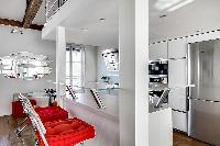 white kitchen bar counter with two tall chairs in a 1-bedroom loft Paris luxury apartment