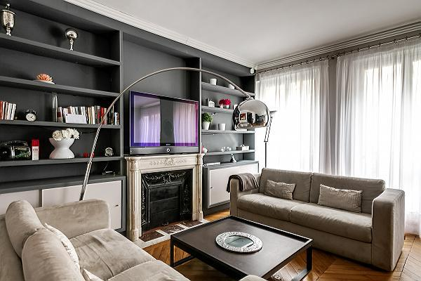 open living area with two large sofas, a center table, built-in shelves, a desk with a chair, a fire