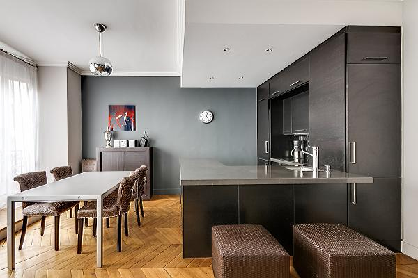 chic dining area with a table and six chairs with fully-equipped kitchen in a 2-bedroom paris luxury