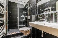 second bathroom with a large sink, a mirror, a toilet, and shower area in Paris luxury apartment