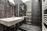 sleek gray-tiled bathroom with a sink, mirror, toilet, and shower area  in Paris luxury apartment