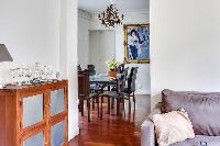 elegant dining area with a long table, six chairs, and paintings in a 3-bedroom Paris luxury apartme