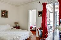 cozy master bedroom with a queen-size bed, a red drape curtain, a study desk with a chair and a lamp