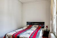 second bedroom with a double bed and bedside tables  in a 3-bedroom Paris luxury apartment