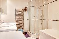 bathroom  with a toilet, a shower area, a sink, a mirror, and a full bathtub  in a 3-bedroom Paris l