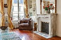 living area with an armchair, a fireplace, and shelves in a 3-bedroom Paris luxury apartment