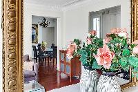 flower vase in front of the mirror in the living room of a 3-bedroom Paris luxury apartment