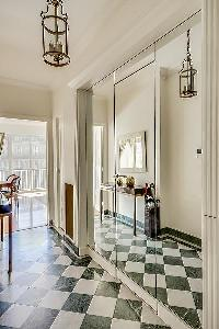 black and white tiled-floor and mirrored walls in a 1-bedroom Paris luxury apartment