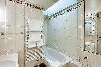 elegant bathroom with a full bathtub, a detachable shower head, built-in cabinets, a sink, and a van