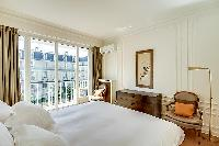 bedroom elegantly furnished with a queen-size bed, a nightstand, two armchairs, a lamp, and air cond