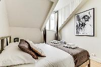 master bedroom with queen-size bed, fresh linens and towels in a 3-bedroom Paris luxury apartment