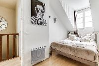 second bedroom with a double bed, fresh linens and towels in a 3-bedroom Paris luxury apartment