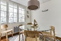 round glass dining table and4 wooden chairs in a 3-bedroom Paris luxury apartment