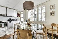 fully-equipped kitchen with four-seater dining set in a 3-bedroom Paris luxury apartment