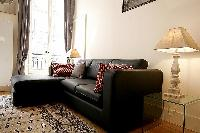 comfortable living room with L-shaped sofa, two armchairs, a center table, and a media shelf with te