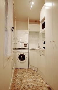 A washing machine, iron, ironing board, and clothes dryer in a 1-bedroom Paris luxury