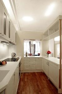 pristine white fully-equipped kitchen in a 1-bedroom Paris luxury apartment