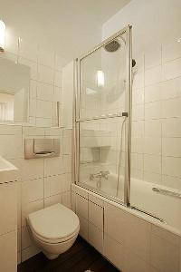 An en-suite bathroom with a toilet, a sink, a mirror, built-in cabinets, and a shower area in a 1-be