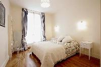 comfortable bedroom with a queen-size bed, two bedside tables, a chair, and a bookshelf in a 1-bedro