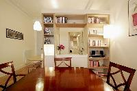 dining area with a four-seater dining set, bookshelves, breakfast bar, and stools in a 1-bedroom Par