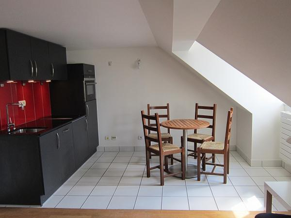 dining area with a round table and four chairs and open kitchen in a studio Paris luxury apartment