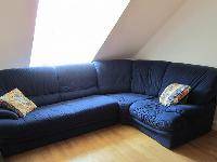 comfortable L-shaped blue sofa in a studio Paris luxury apartment