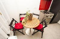 modern well-equipped kitchen with small dining table and 4 seats in a 2-bedroom Paris luxury apartme