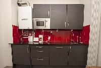 modern well-equipped kitchen in ed and gray hues in a 2-bedroom Paris luxury apartmentmodern well-eq