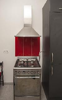 modern well-equipped kitchen in ed and gray hues in a 2-bedroom Paris luxury apartment