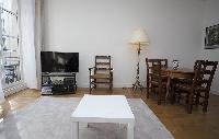 cozy living area with a center table, a chair, a TV and a lamp in a 2-bedroom Paris luxury apartment