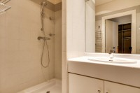 second bedroom fully-equipped with a shower, a sink, a toilet, and a mirror in a 2-bedroom Paris lux