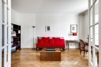 a study room with a second sofa, a study desk and table, chairs, and cabinets in a 2-bedroom Paris l
