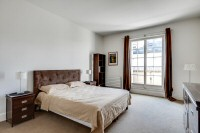 master bedroom is furnished with a queen-size bed, a large cabinet, a shelf, a nightstand, and two b