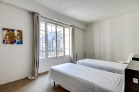 second bedroom with two single beds and a built-in closet in a 2-bedroom Paris luxury apartment
