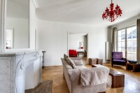 living area furnished with a sofa, an armchair, and a media shelf with television in a 2-bedroom Par
