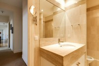 first bathroom elegantly furnished with a sink, a mirror, a toilet, and a full bathroom with a detac