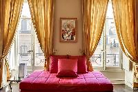 comfortable red sofa and elegant curtains in a 1-bedroom Paris luxury apartment